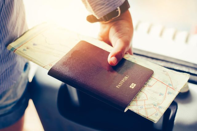 Tourists handle passports and suitcases to prepare for the trip.