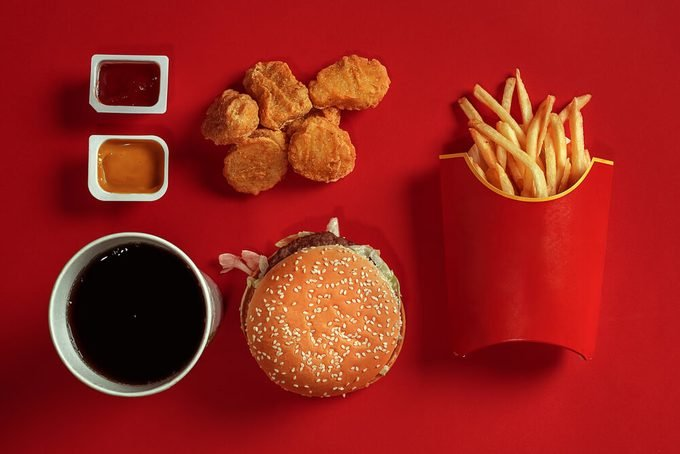 Concept of mock up burger, potatoes, sauce, chicken nuggets and drink on red background. Copy space for text and logo.