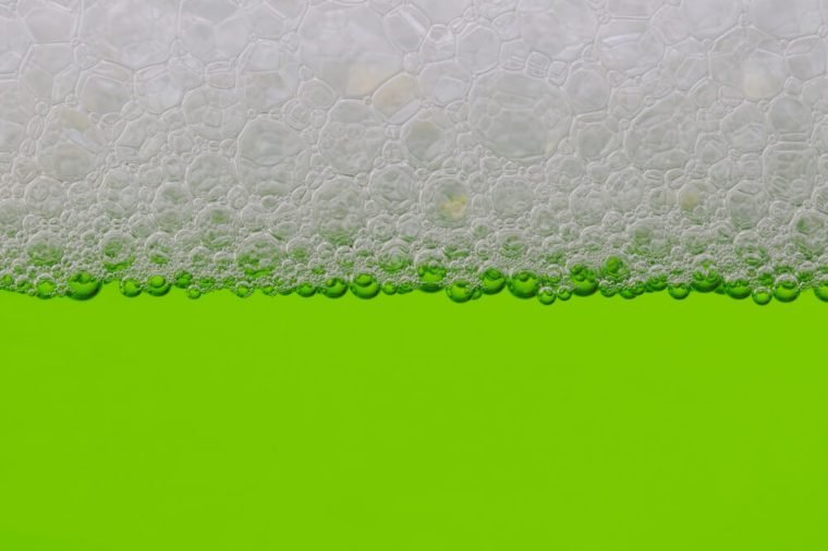 Closeup of a green liquid with a line of bubbles at the top.