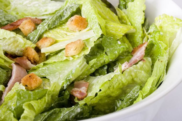 Close up Caesar salad with homemade croutons, sliced bacon, parmesan cheese and Caesar dressing in large ceramic white bowl.