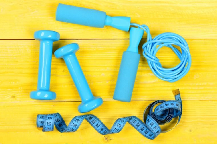 Dumbbells, measuring tape and jump rope, top view. Sports equipment on wooden yellow background. Barbells and centimeter near tools for weight loss. Workout and active lifestyle concept.