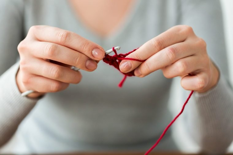 people and needlework concept - woman hands knitting with crochet hook and red yarn