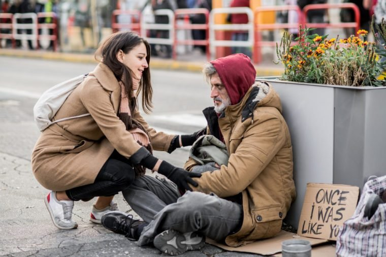 Young woman giving money to homeless beggar man sitting in city.