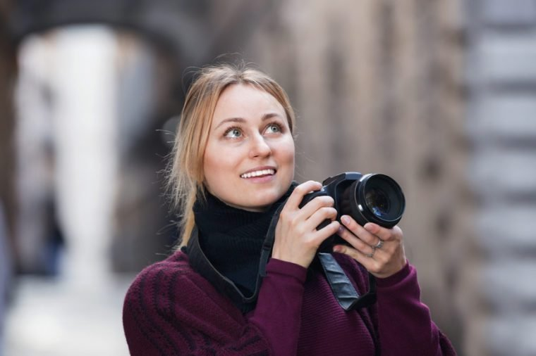 Happy smiling girl taking picture with camera in the town
