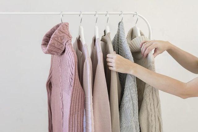 Woman choosing pastel warm cozy sweaters on hangers