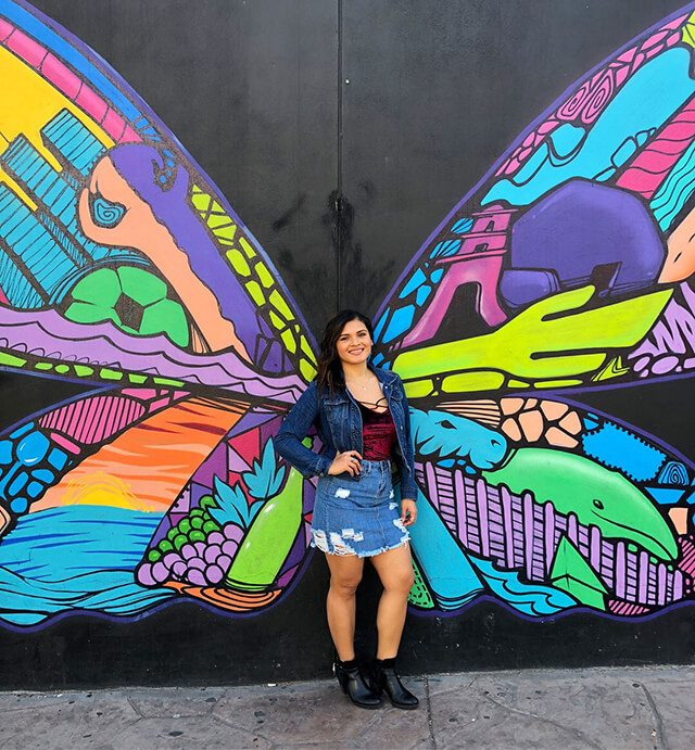 Laura Gonzlaez in front of colorful butterfly wings