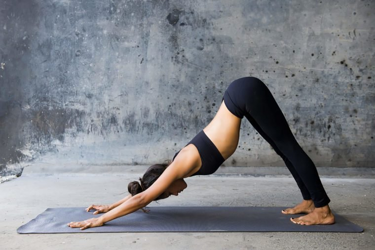 woman in black yoga gear in downward dog pose