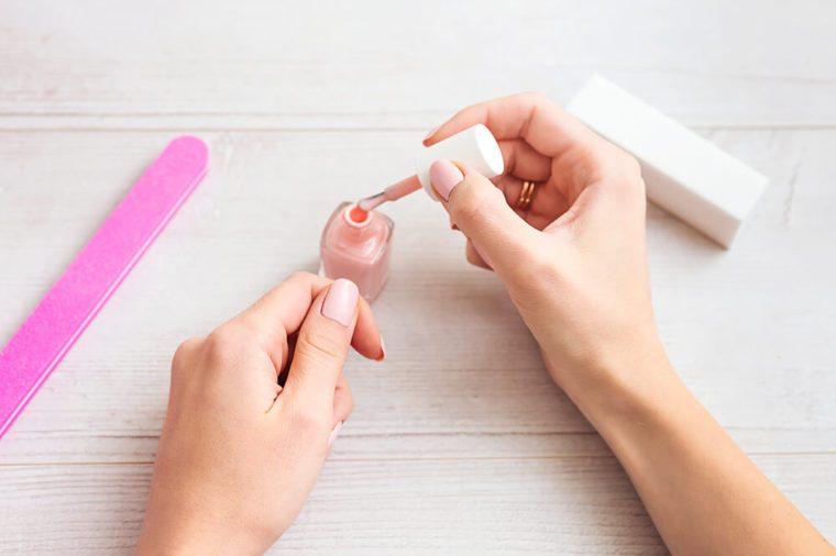 Female hands applying light pink nail polish on wooden table with nail set. Manicure nail paint pink color.
