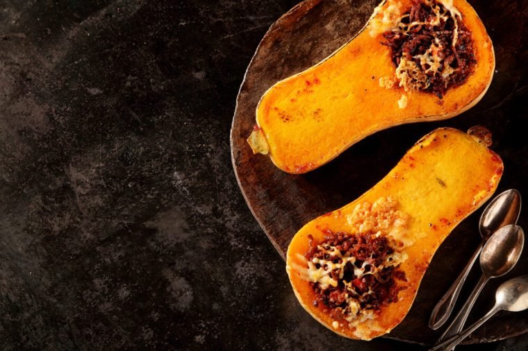 Halved roasted butternut squash with spicy filling viewed overhead on a rustic flat metal plate with spoons and copyspace for healthy seasonal autumn cuisine