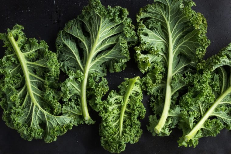 fresh green organic kale leaves on dark background. top view.