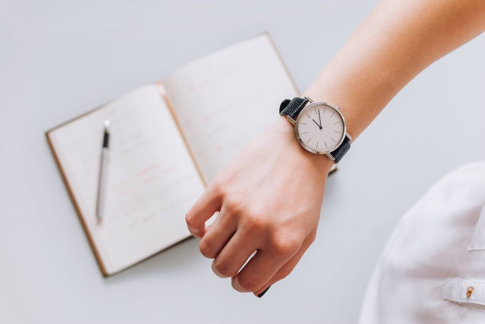 A young business woman checks time on her classic watch, she thinks about time management and corrects schedule in her diary