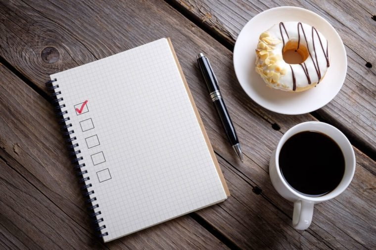 Book with blank checklist with coffee and donuts on rustic wooden table