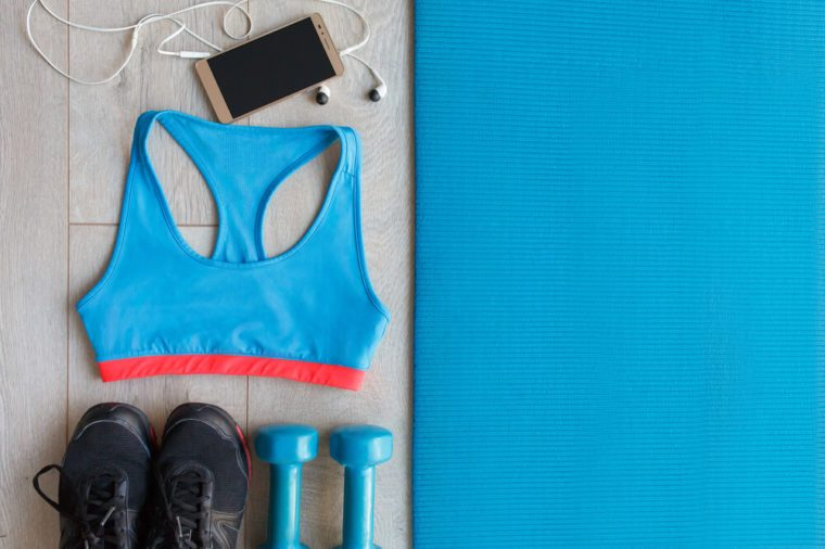 View from above of Fitness and sport equipment. Healthy lifestyle concept. Sneakers, sportswear, dumbbells, cell phone and headphones on blue mat wooden floor background, top view