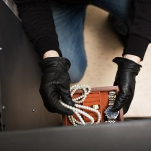 theft, burglary and people concept - thief stealing valuables from safe at crime scene