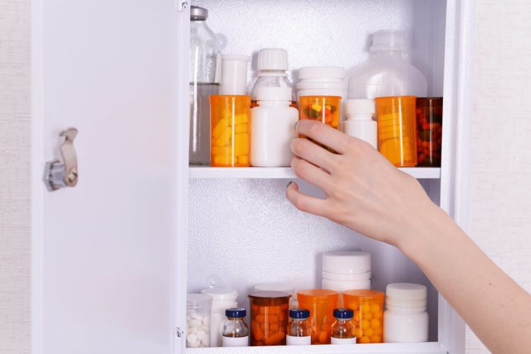 Female hand taking pills from medicine chest, closeup