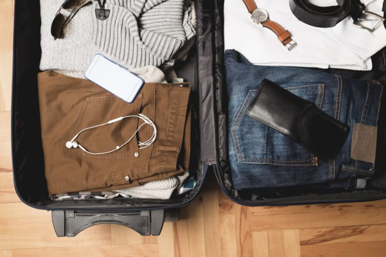 Open traveler's bag with men clothing, accessories, watch, watch and belt. Travel and vacations concept.