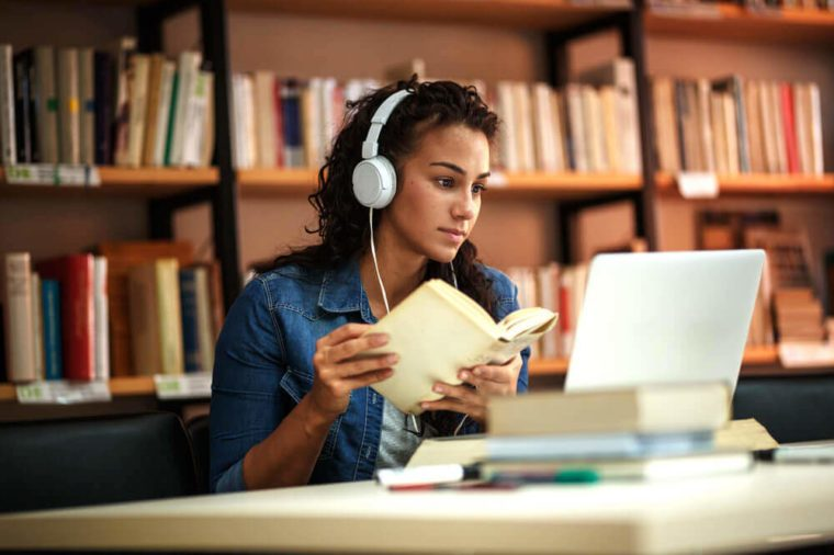 Young female student study in the school library.She using laptop and learning online.