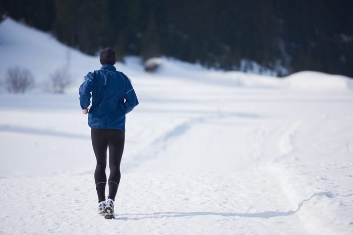 young man jogging on snow in forest, bautiful sunny winter day. handsome sporty ahtlete man running
