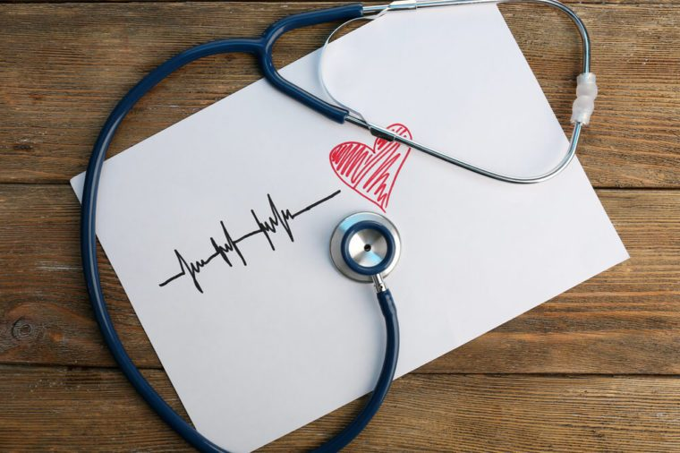 Stethoscope with heart on wooden background