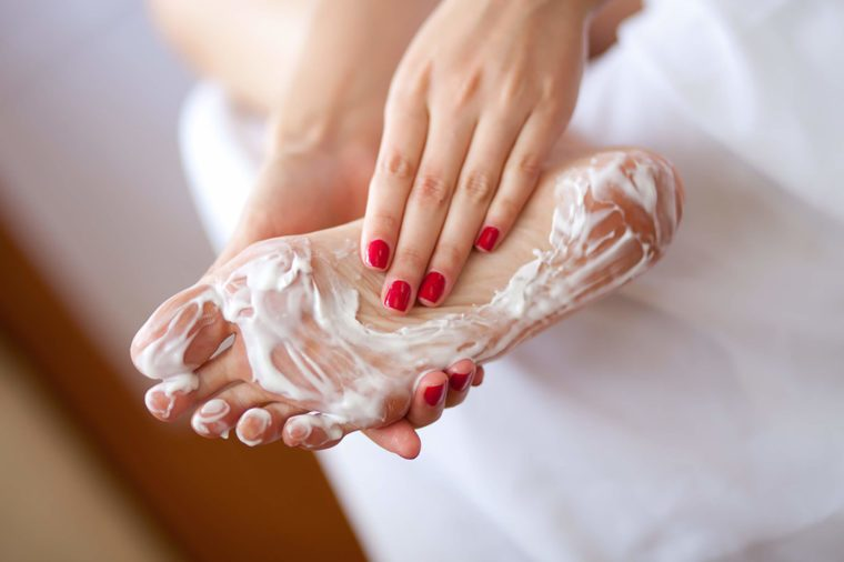woman rubbing lotion on the sole of her foot