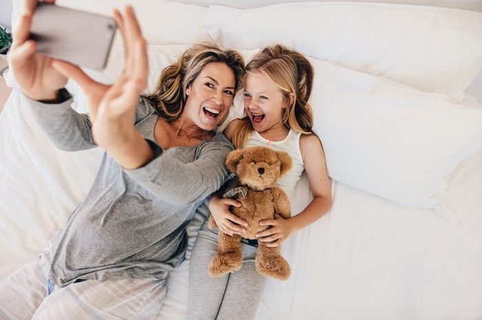Happy young mother taking selfie with her daughter. Young family taking selfie on bed at home.