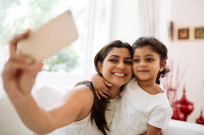 Smiling mother and daughter bonding together to take a selfie