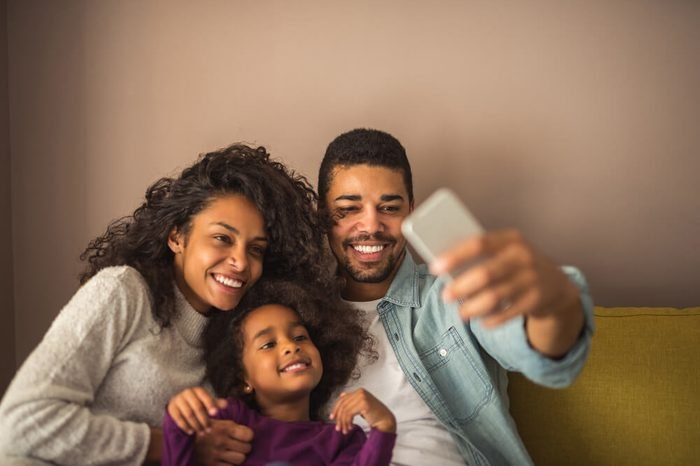 African american family taking pictures with mobile phone at home.