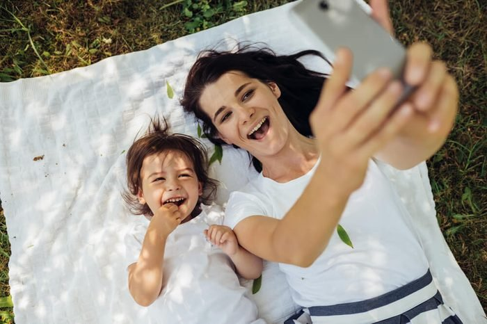 Happy brunette young smiling woman taking self-portrait to beautiful little girl daughter lying on white plaid on grass. Young family taking selfie outdoor. Motherhood, parenting and childhood concept