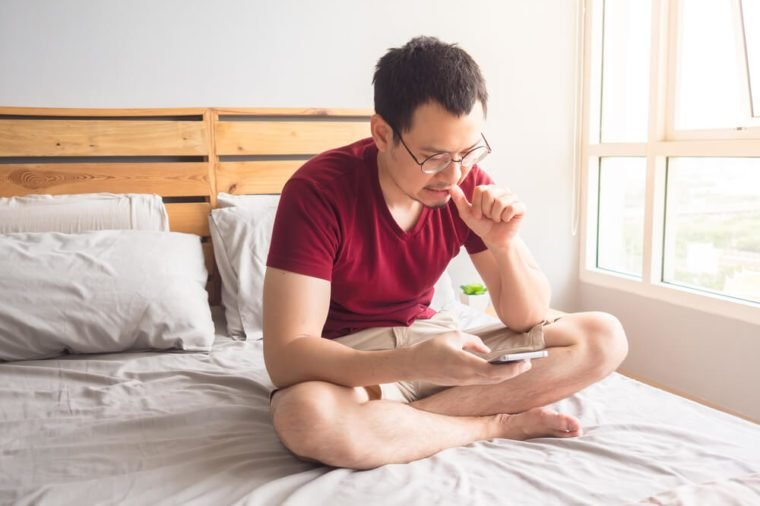 Lonely non-social Asian man with his smartphone in his bedroom apartment. Man bites nails.