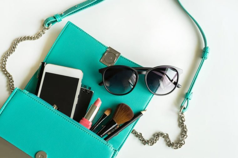 Woman handbag with makeup, cellphone and accessories on white background, Fashion concept