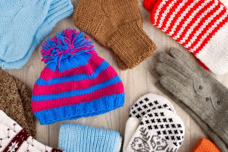 Knitted clothes. Hat, gloves, mittens, scarves for cold seasons. Warm clothes. Knitted clothes of different colors. Hat, mittens, scarves, gloves, socks from the cold. View from above.