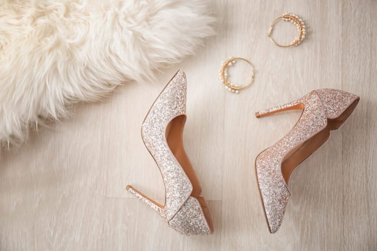 Pair of sparkly female shoes and elegant earrings on floor, top view
