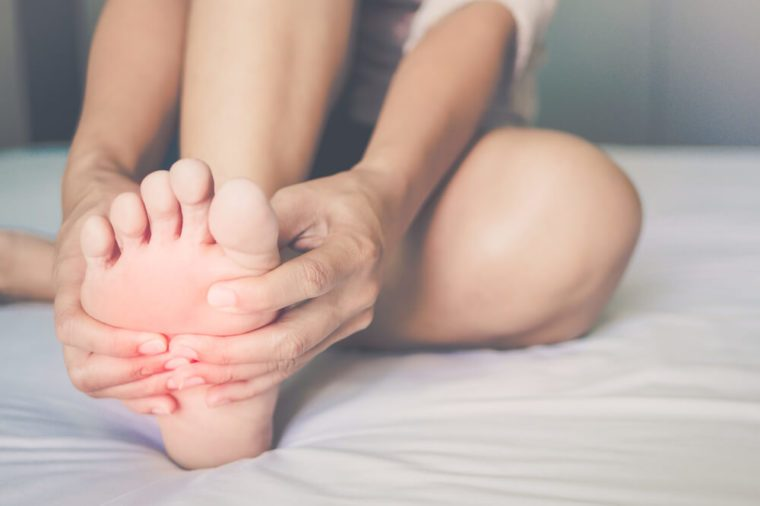 Health care concept. Woman massaging her painful, red illuminated foot in the area of ​​pain.
