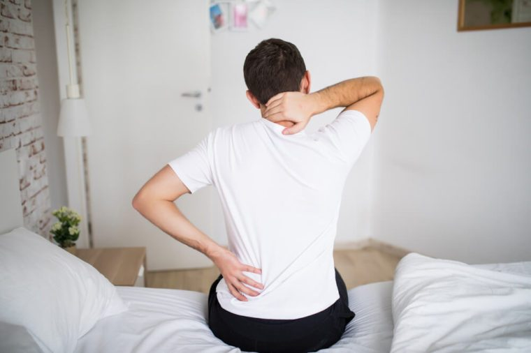 Man suffering from backache at home in the bedroom.