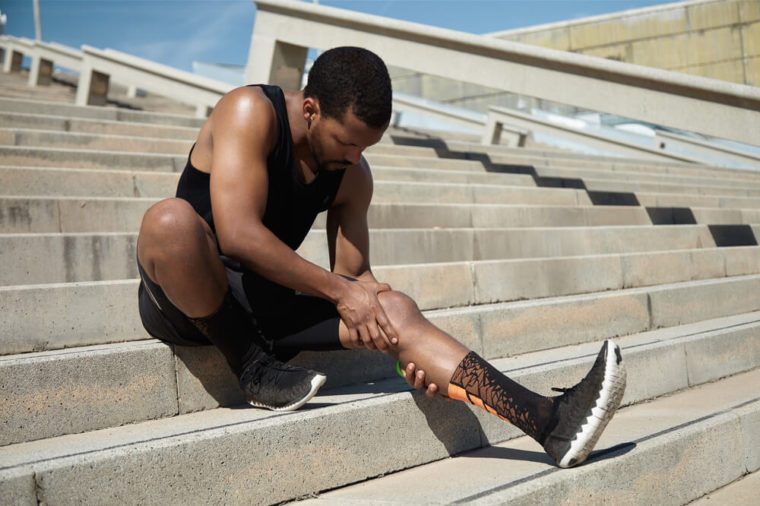 Beautiful black runner with a muscular athletic body holding his leg with both hands, feeling pain in the knee or calf, massaging, suffering from tension or spasm while sitting on the steps of a concrete staircase
