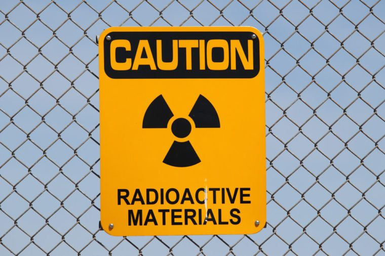 "A ""Caution - Radioactive Materials"" sign on a fence."