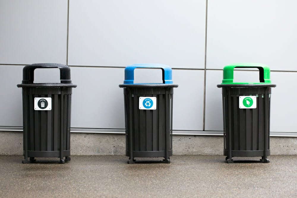 Row of trash bins with garbage, recycling, and compost cans along a wall