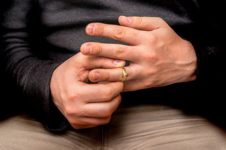 Disappointed man is taking off his wedding ring isolated on black - divorce concept