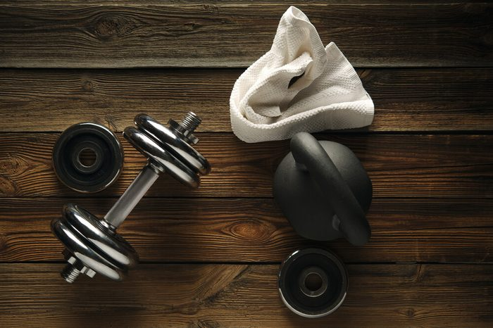 Top view of black iron kettlebell, dumbbell and white towel on wooden floor Sport background with copyspace Weight lifting exercise concept.