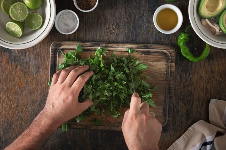 man slicing cilantro on a wooden cutting board
