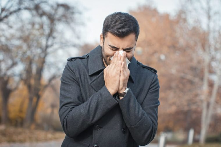 Young man wearing jacket suffering from cold and holding handkerchief on nose