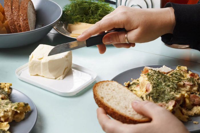 A female hand buttering bread