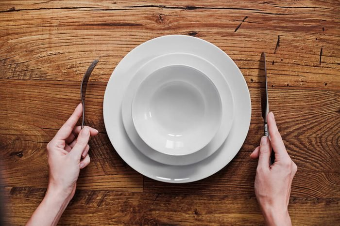 Healthy food theme: hands holding knife and fork on a plate, top view