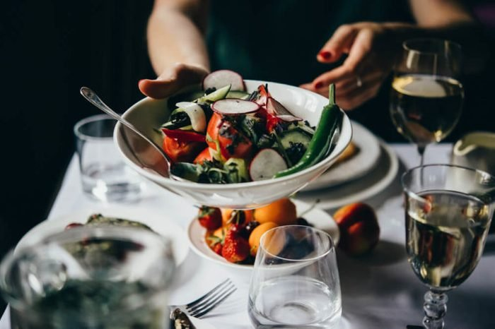 Hands passing over a bowl of salad served during a dinner of a party in a restaurant.