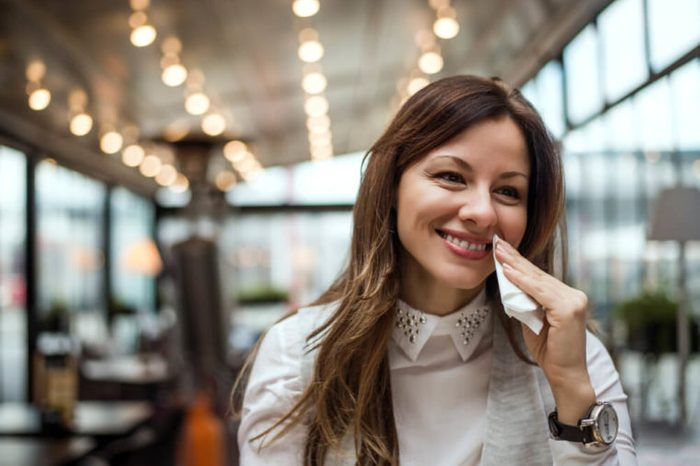 Beautiful young woman in the restaurant, wipes mouth with a napkin.
