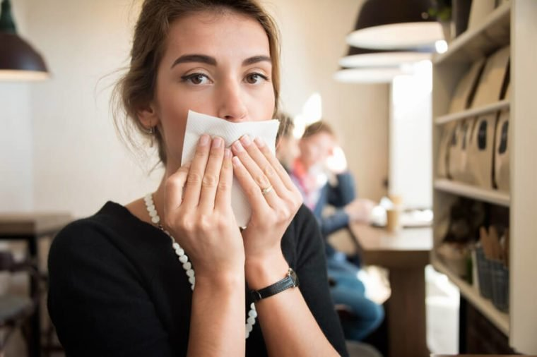 Girl in the cafe, wipes his mouth with a napkin