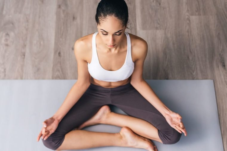 Concentration and meditation. Top view of beautiful young African woman in sportswear practicing yoga while sitting in lotus position on the floor