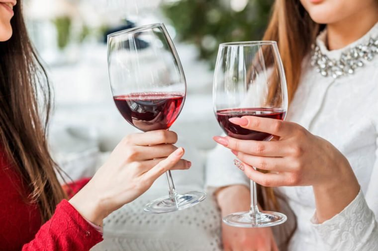 Two female friends drinking wine in restaurant