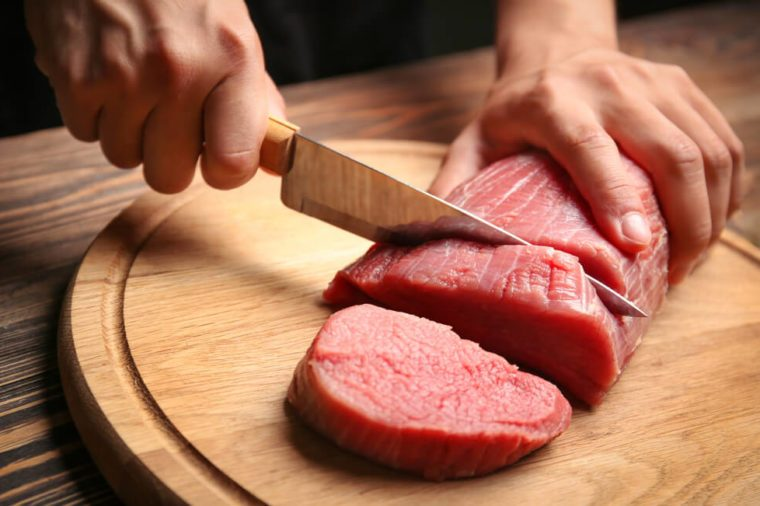 Chef cutting fresh raw meat on wooden board