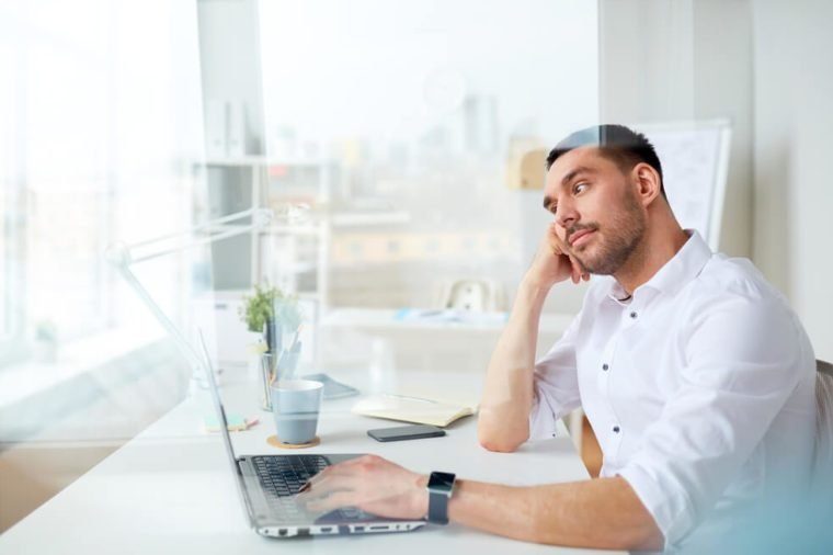 business, people, deadline and technology concept - businessman with laptop computer thinking at office